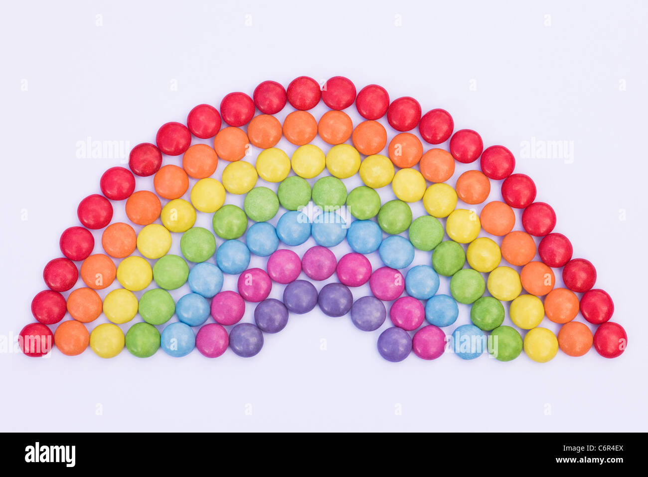 Rainbow smartie pattern on a white background. - Stock Image