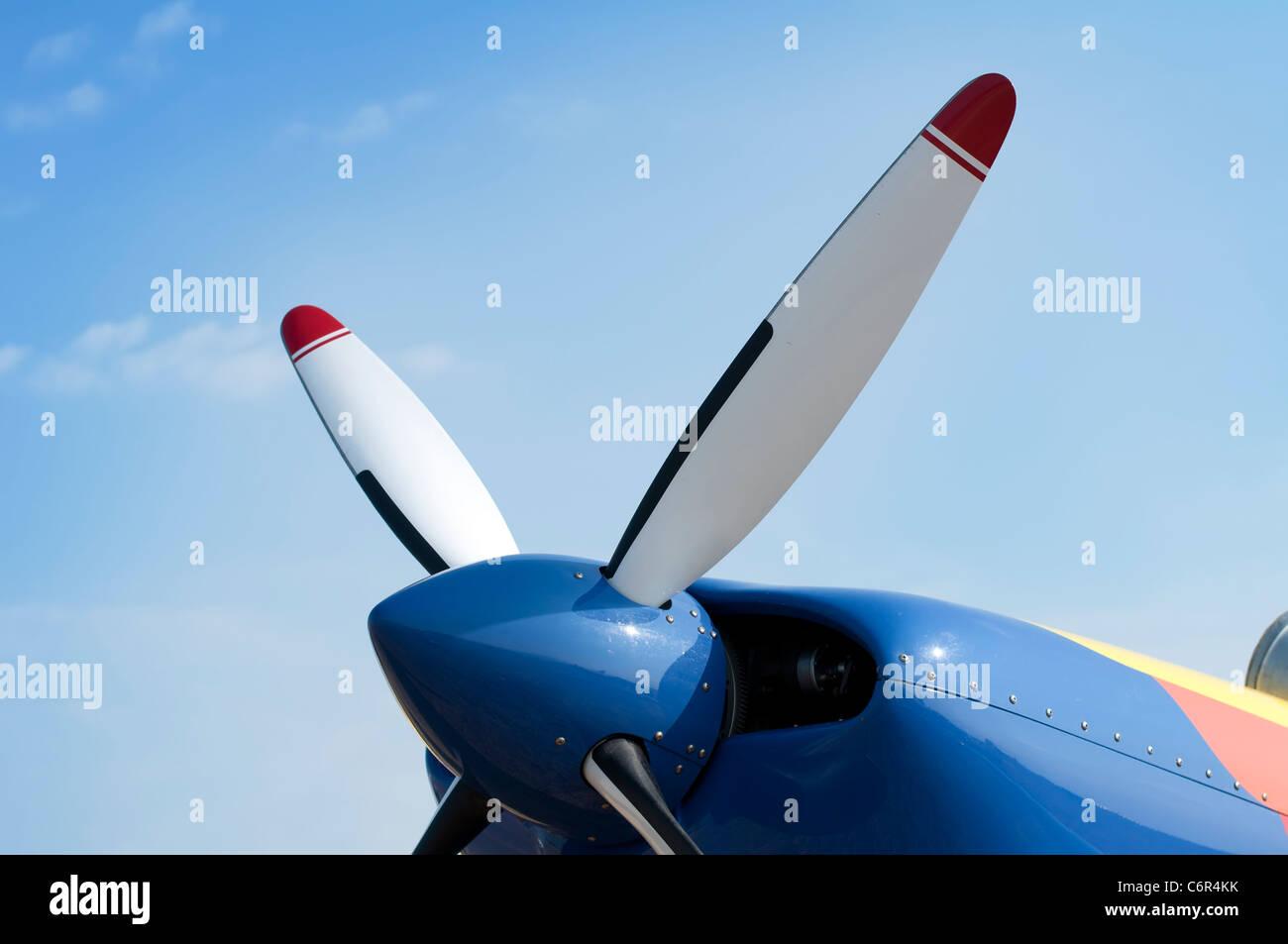 White plane propeller on blue sky background - Stock Image