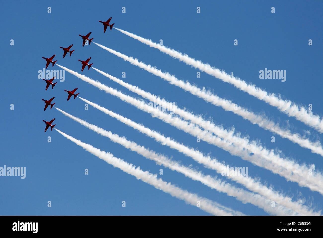 'Red Arrows' flying in 'Big Vixen' formation with white [vapour trails] against cloudless blue sky, - Stock Image