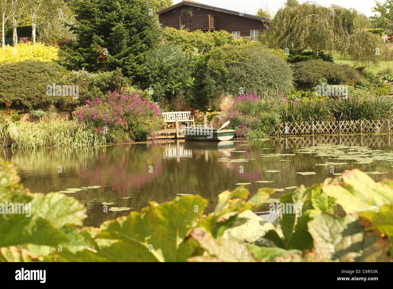 Small lake in an English country garden, with boat Stock Photo ...