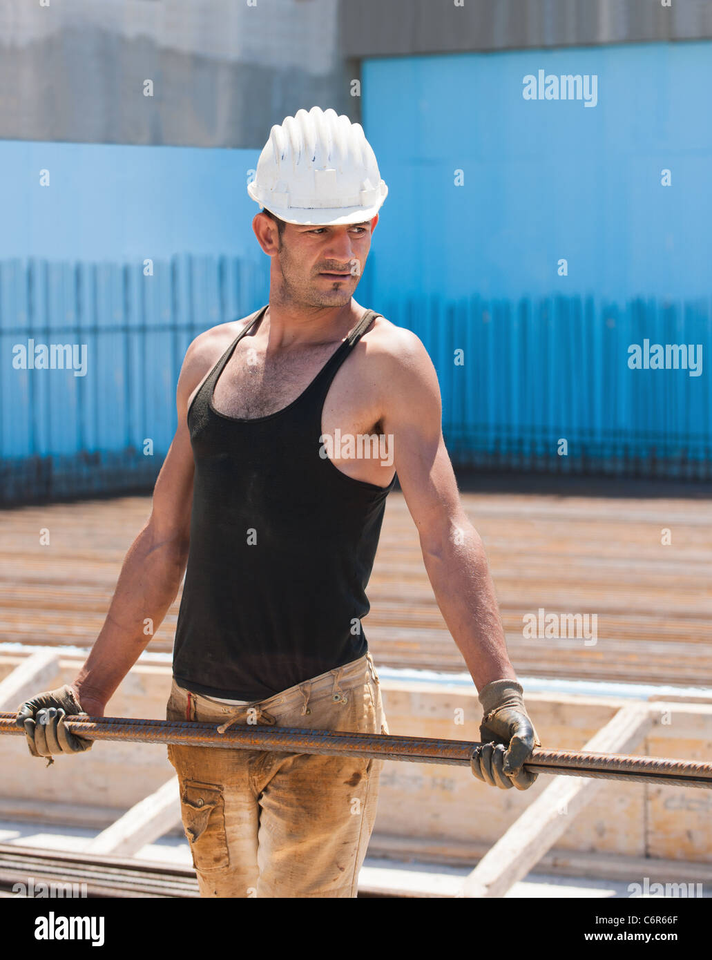 Construction worker carrying reinforcement steel bars - Stock Image