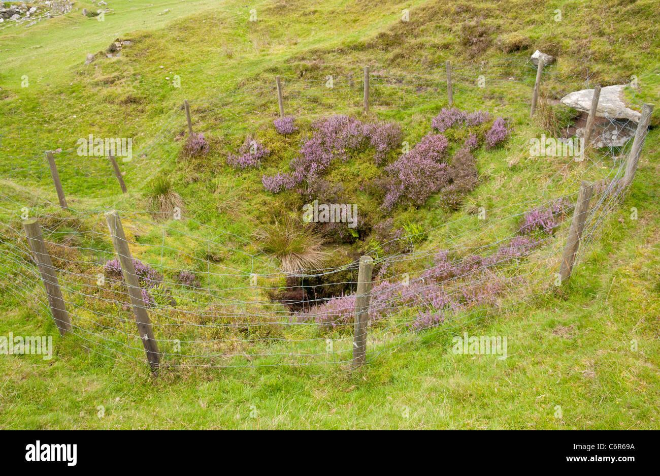 Fenced off mine shaft at Eylesbarrow disused tin mine, Dartmoor, Devon UK - Stock Image