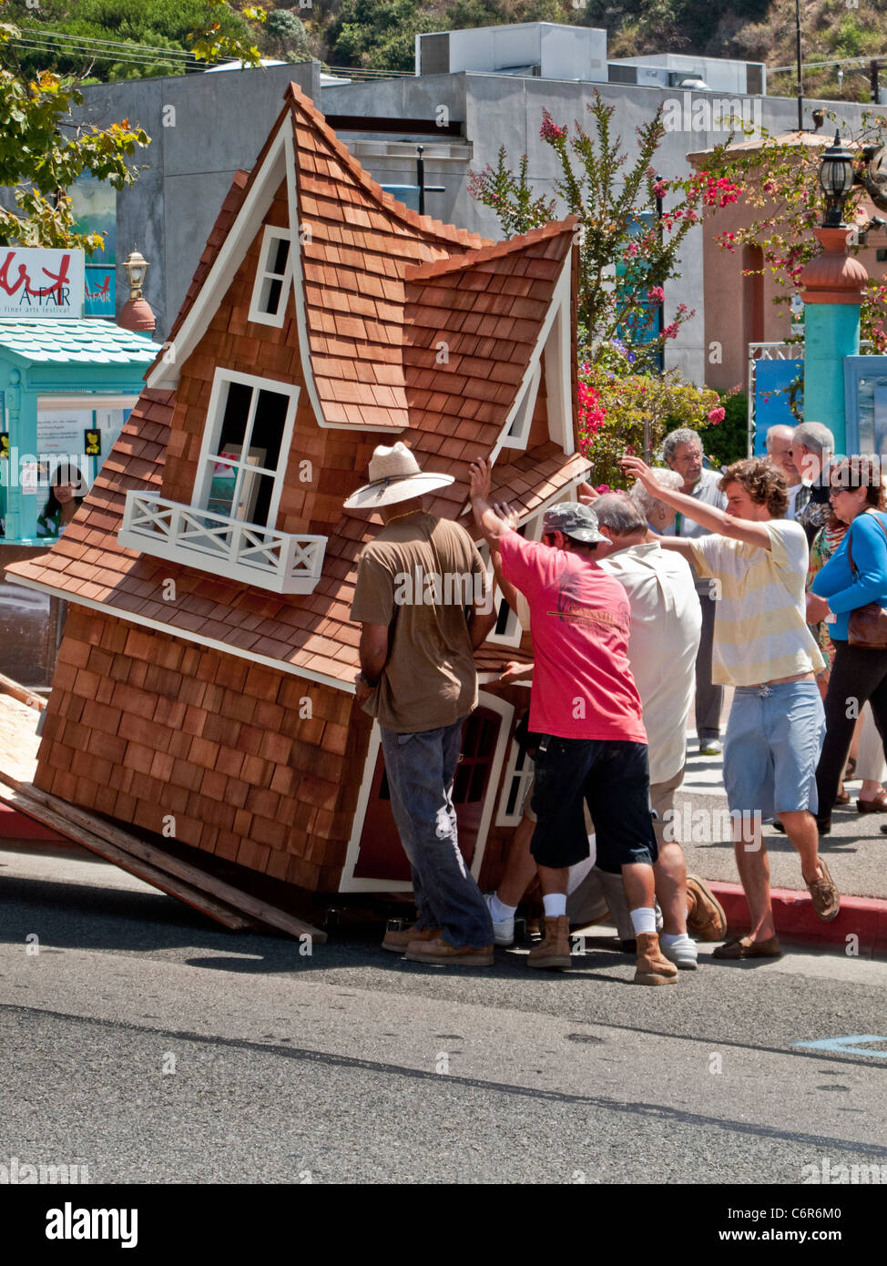 Workmen unload a fanciful doghouse from a truck outside an art show in Laguna Beach, CA. - Stock Image