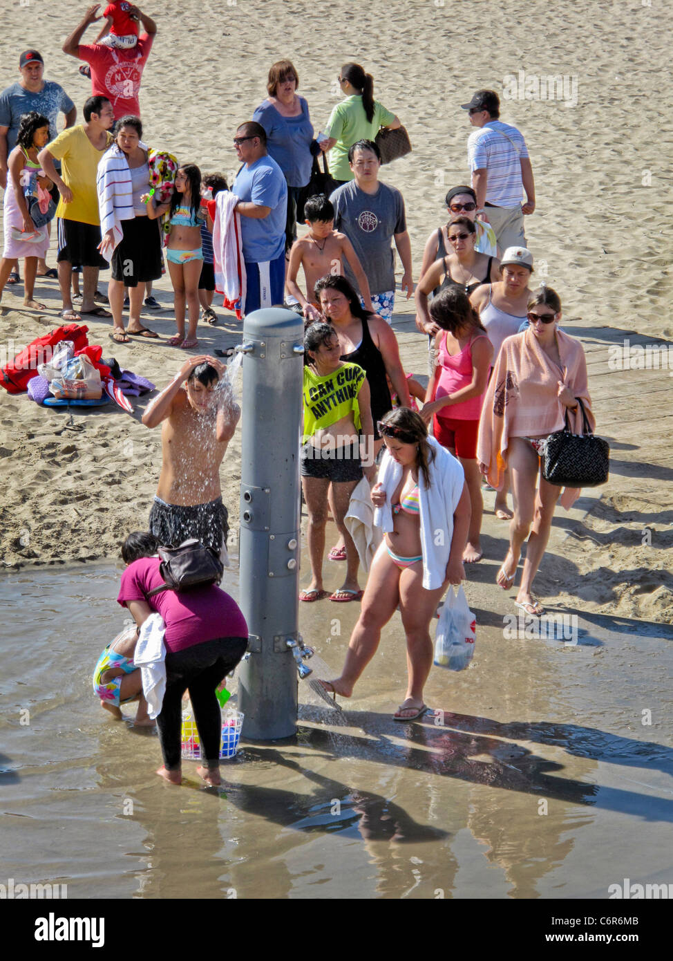 A weekend summer crowd of different ages and ethnicities lines up at a fresh water shower on the beach in Santa - Stock Image