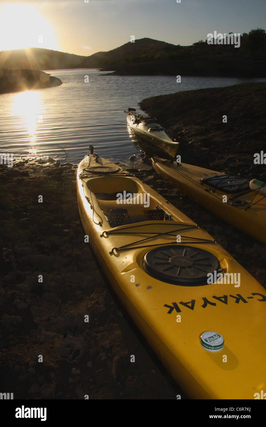 Kayaks on the banks of Van Der Kloof Dam at sunrise - Stock Image