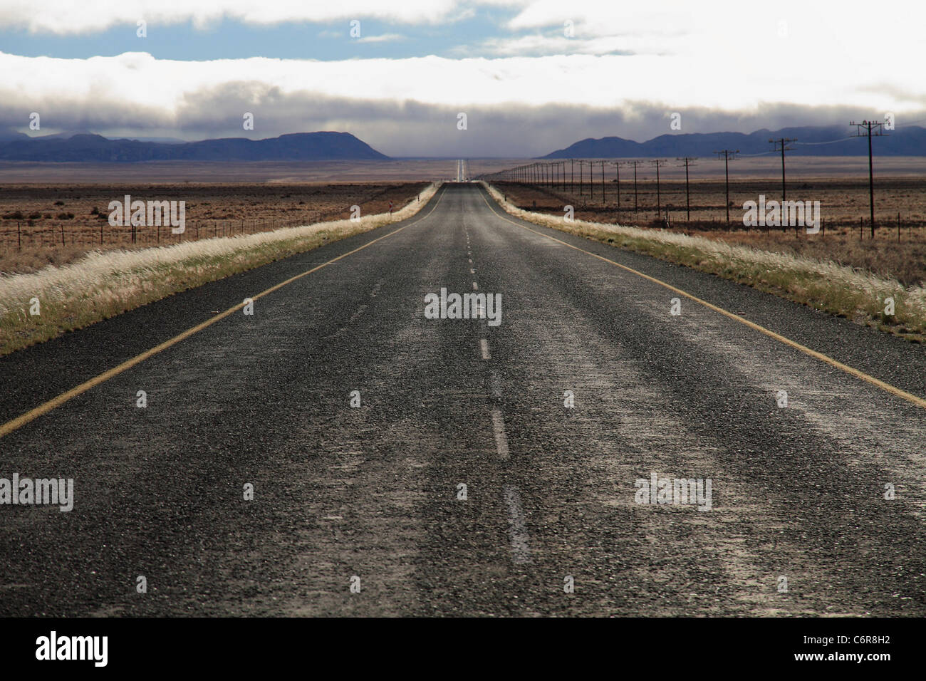 Tar road in remote landscape with motorcycle - Stock Image