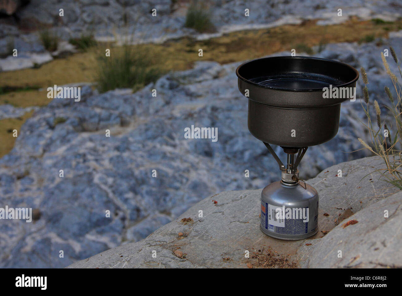Camping stove and pot on rock ledge - Stock Image