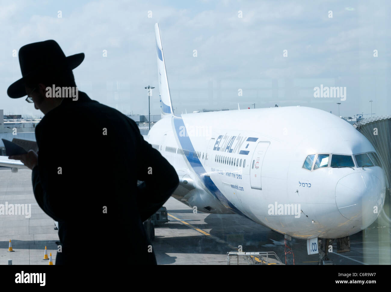 Orthodox Jew praying with El Al plane in Bkgd. Heathrow airport. London - Stock Image