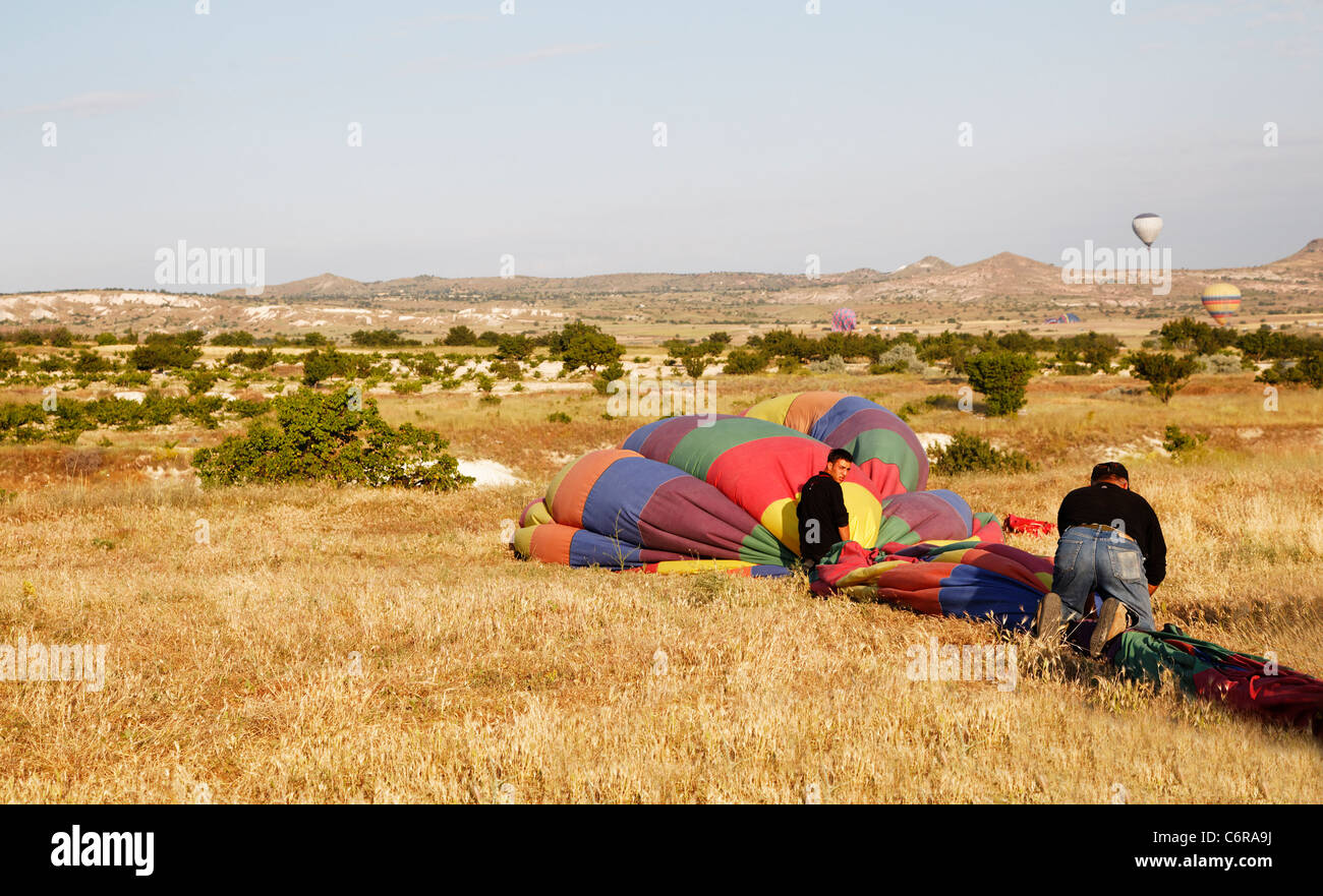 Cappadocia, Turkey - June, 2011: hot air balloons landing after flight and roadies packing them away for storage, - Stock Image