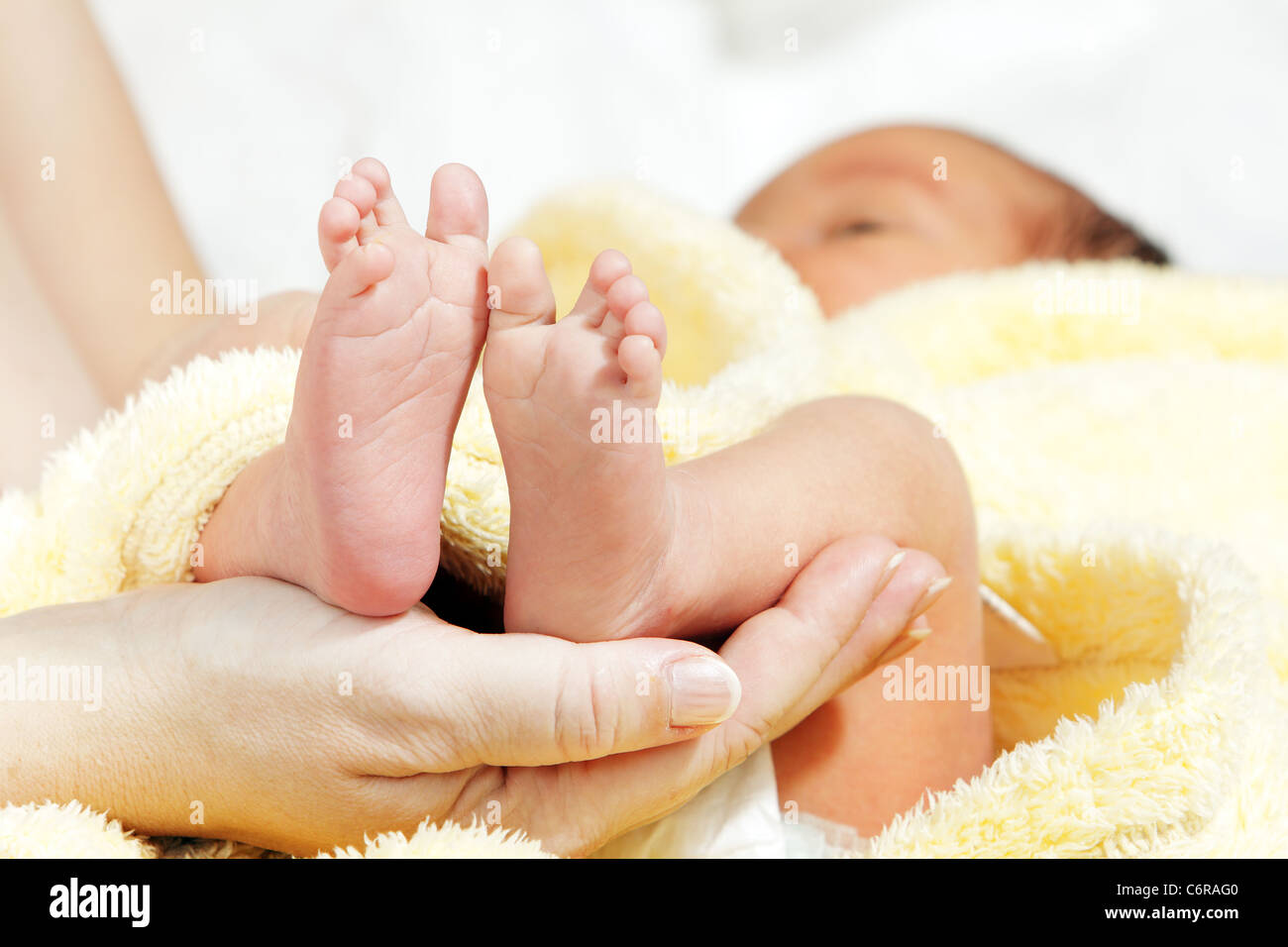 Newborn baby feet in mother's hands with soft yellow blanket