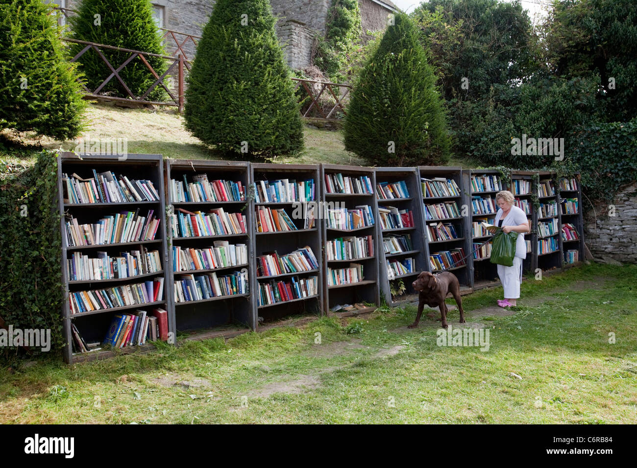 A woman browsing at an honesty bookshop in the grounds of Hay Castle in Hay-On-Wye, UK - Stock Image