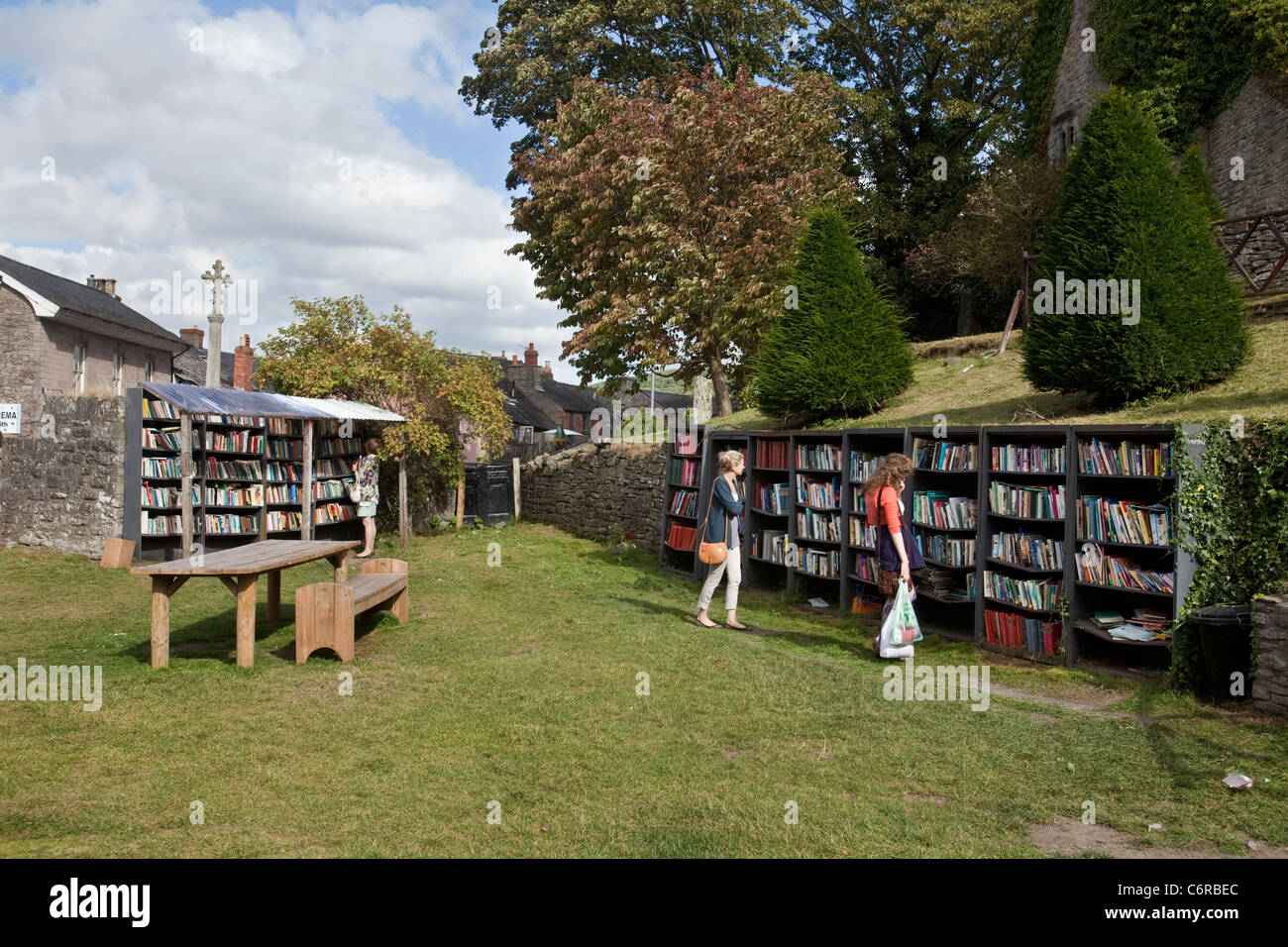 Two people browsing at an honesty bookshop in the grounds of Hay Castle in Hay-On-Wye, UK - Stock Image