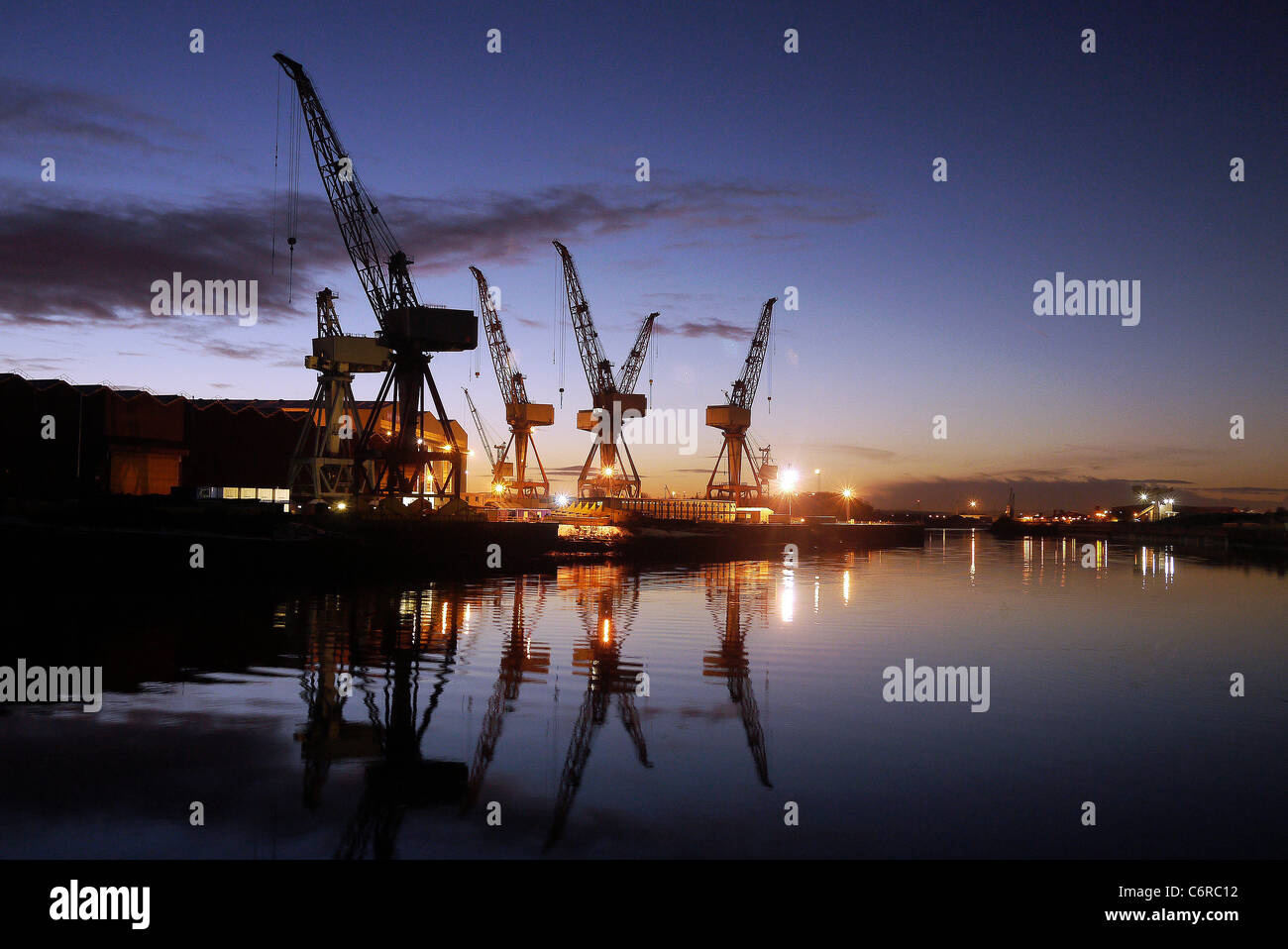 Cranes at the BAE Shipyard on the River Clyde, Glasgow, Scotland silhouetted  against the night sky. - Stock Image