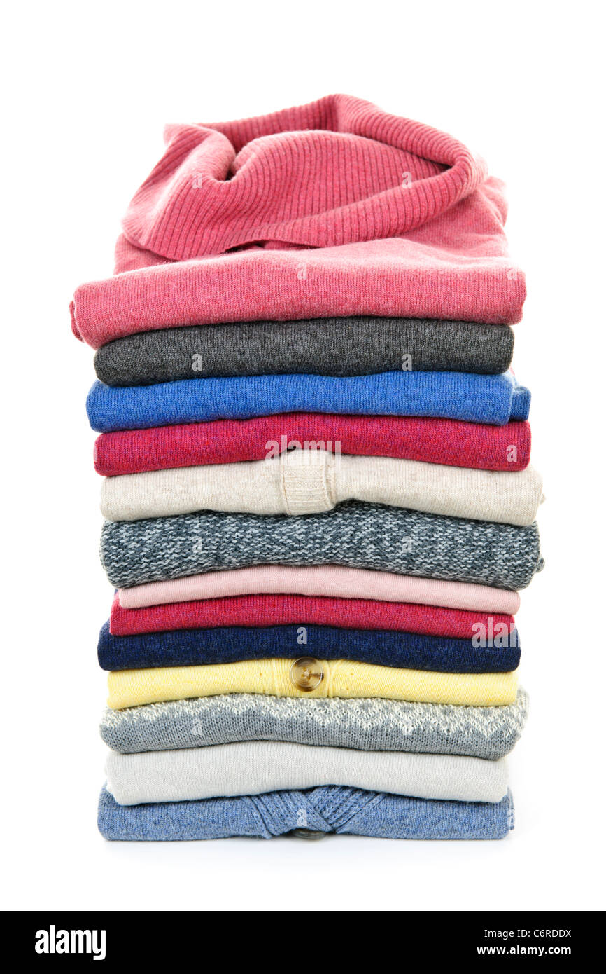 Stack of warm sweaters isolated on white background - Stock Image
