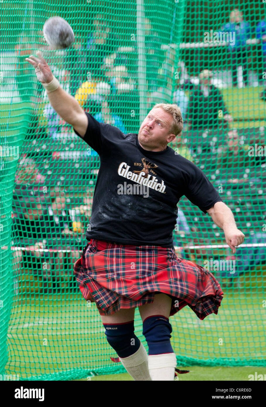 A heavy in a kilt competes in the stone throwing event at the Braemar Highland Gathering in Scotland - Stock Image