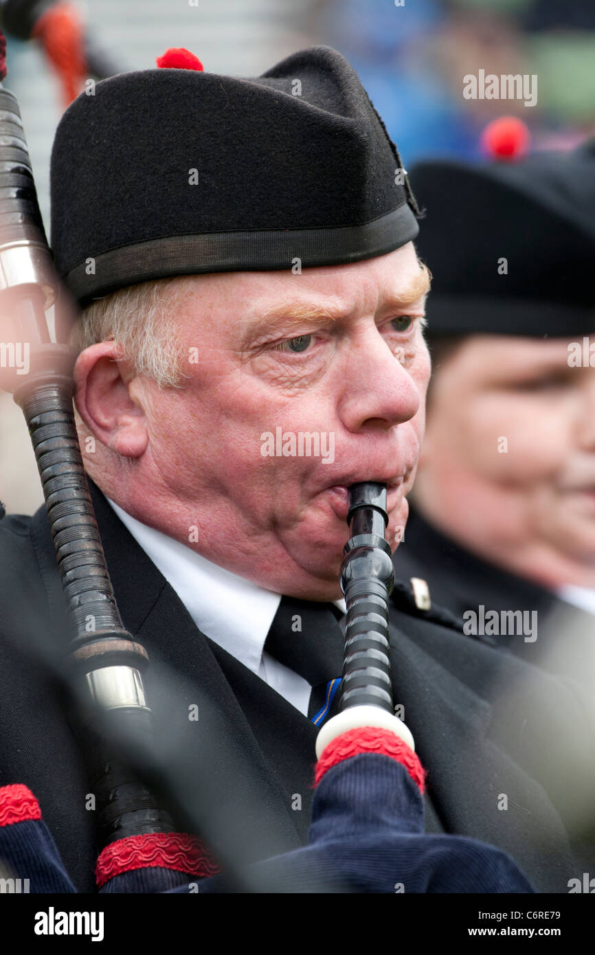 Portrait of a Scottish piper blowing into his bagpipes at the Braemar Highland gathering in Scotland - Stock Image