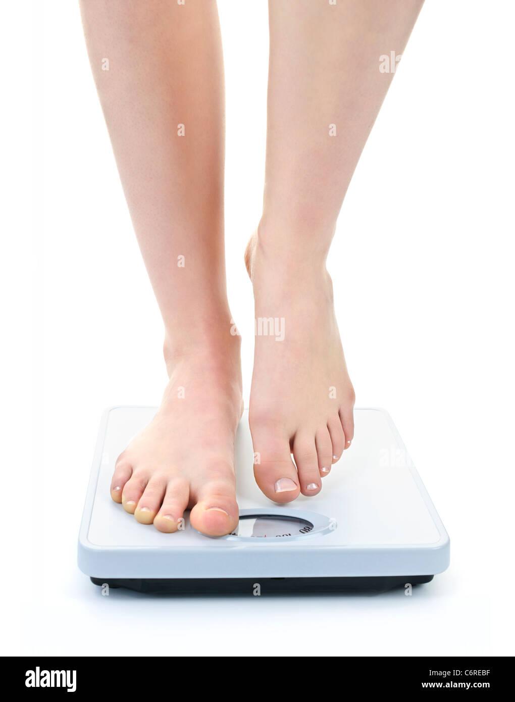 Bare female feet standing on bathroom scale - Stock Image