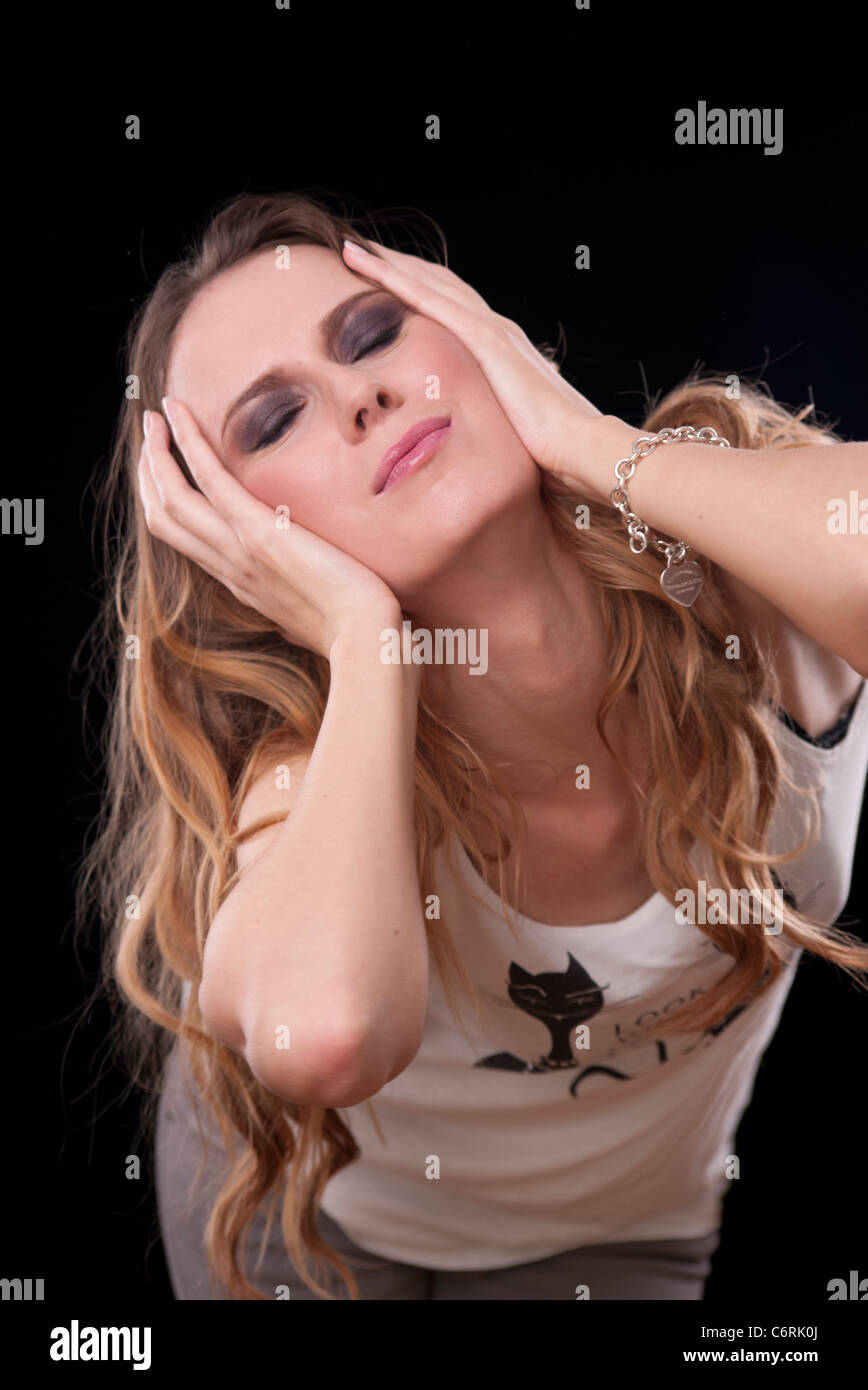woman holding her head in her hands - Stock Image