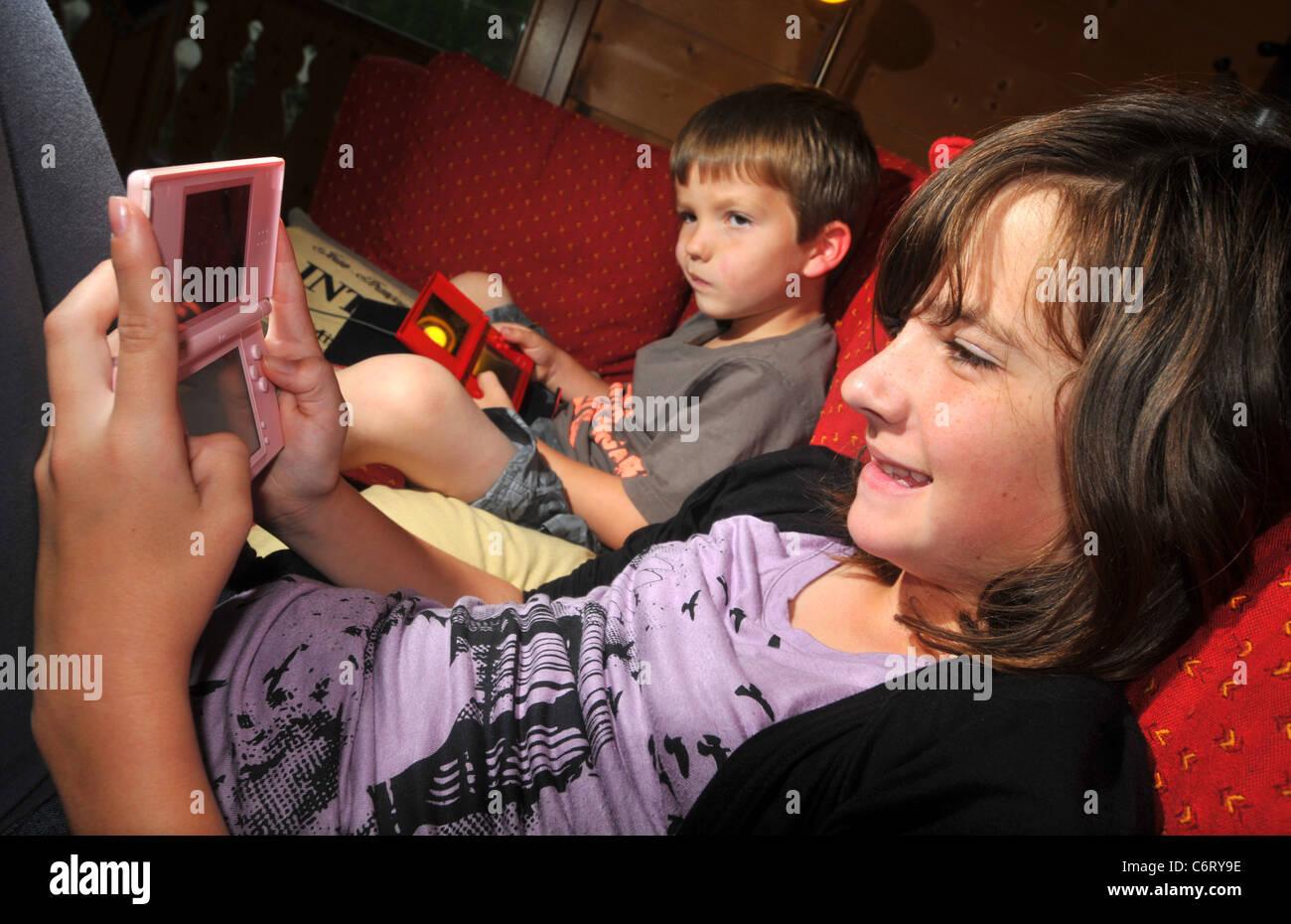 Children play Nintendo DS lite computer game - Stock Image