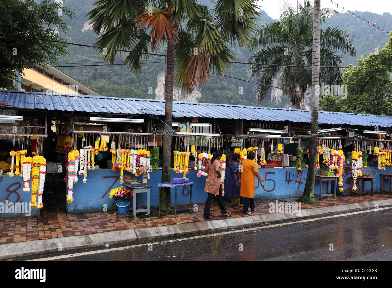 Stalls selling floral offerings to the Hindu gods, outside Batu Caves. - Stock Image