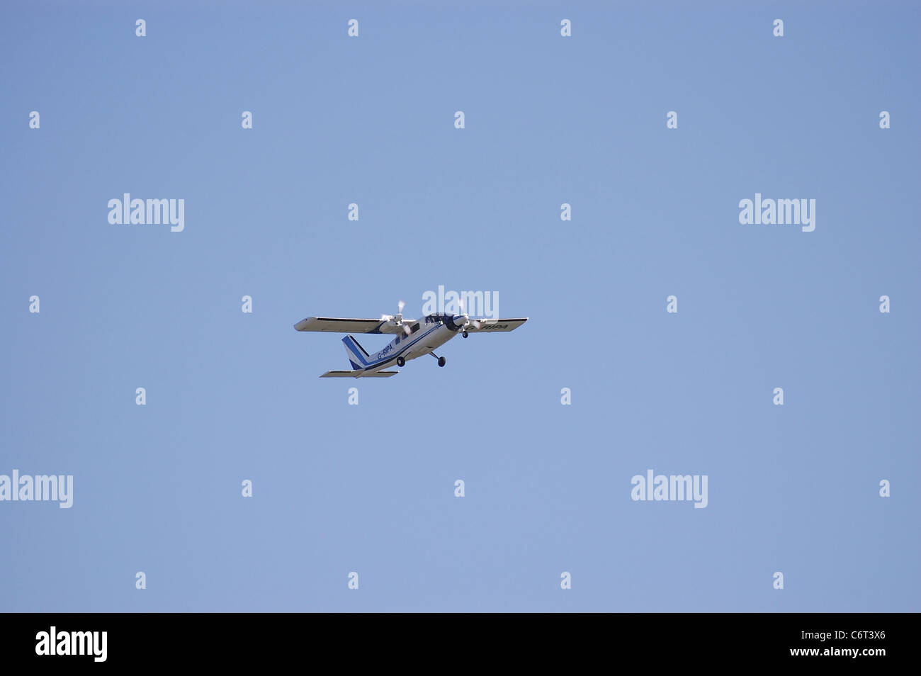 Twin engined propeller aircraft in flight - Stock Image