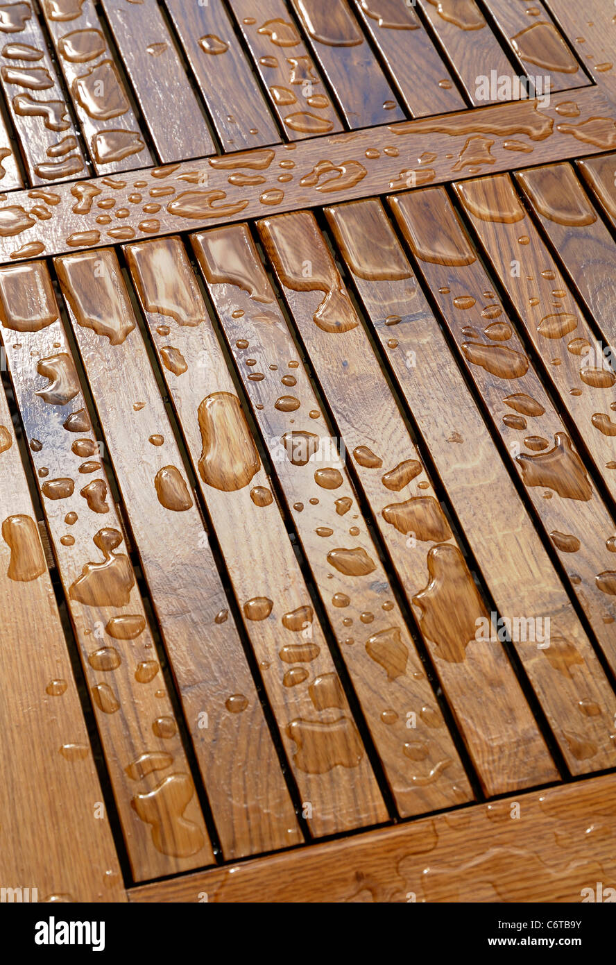 raindrops on wooden garden table - Stock Image