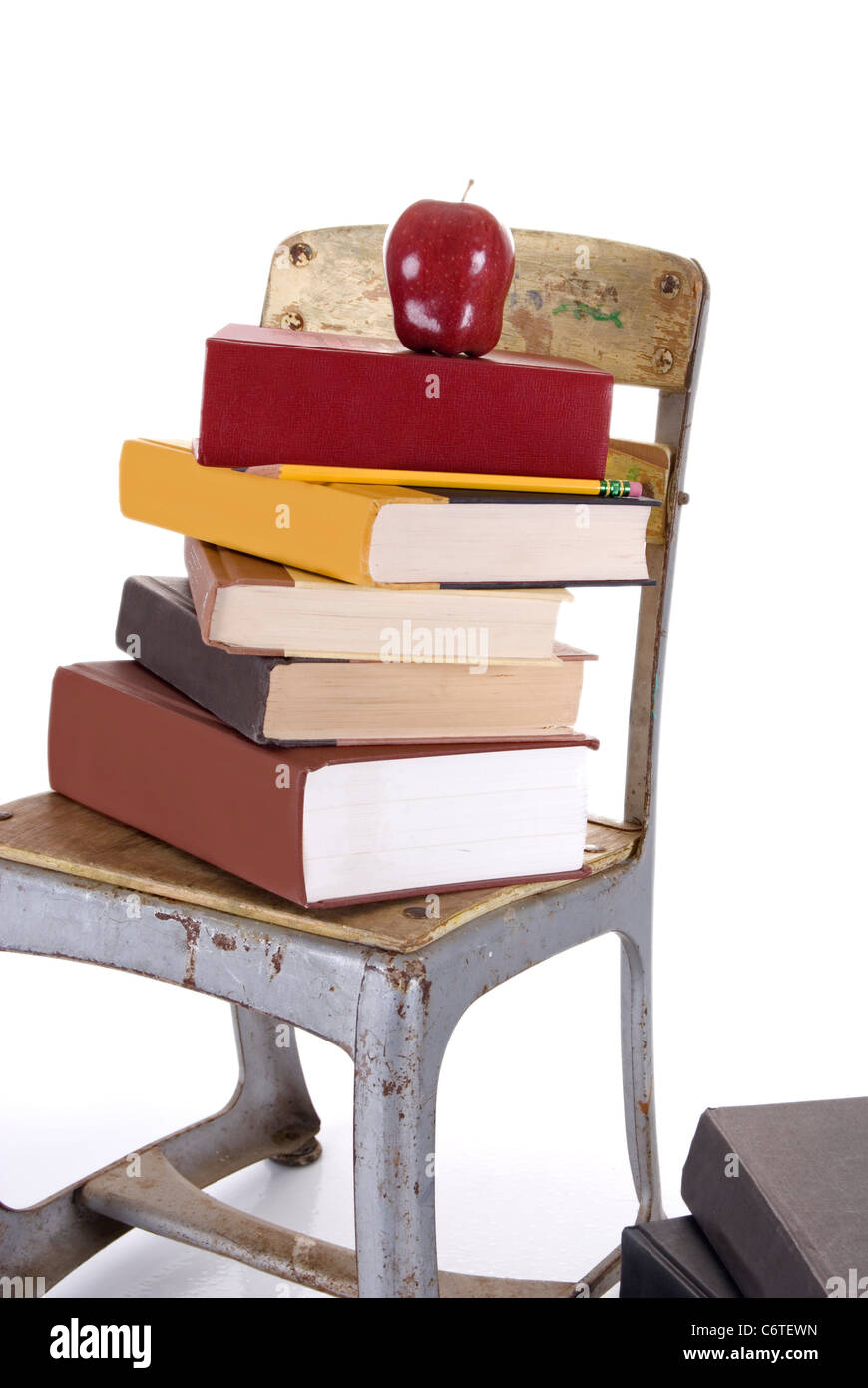 a vintage child s school chair holding a stack of books with a red