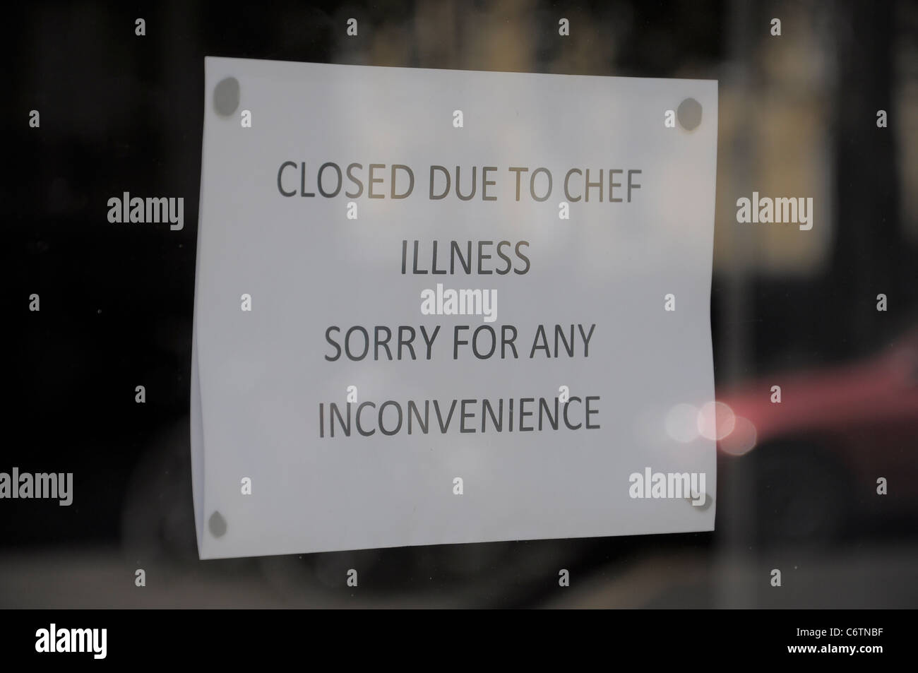 Closed notice in shopping window due to chef illness. - Stock Image