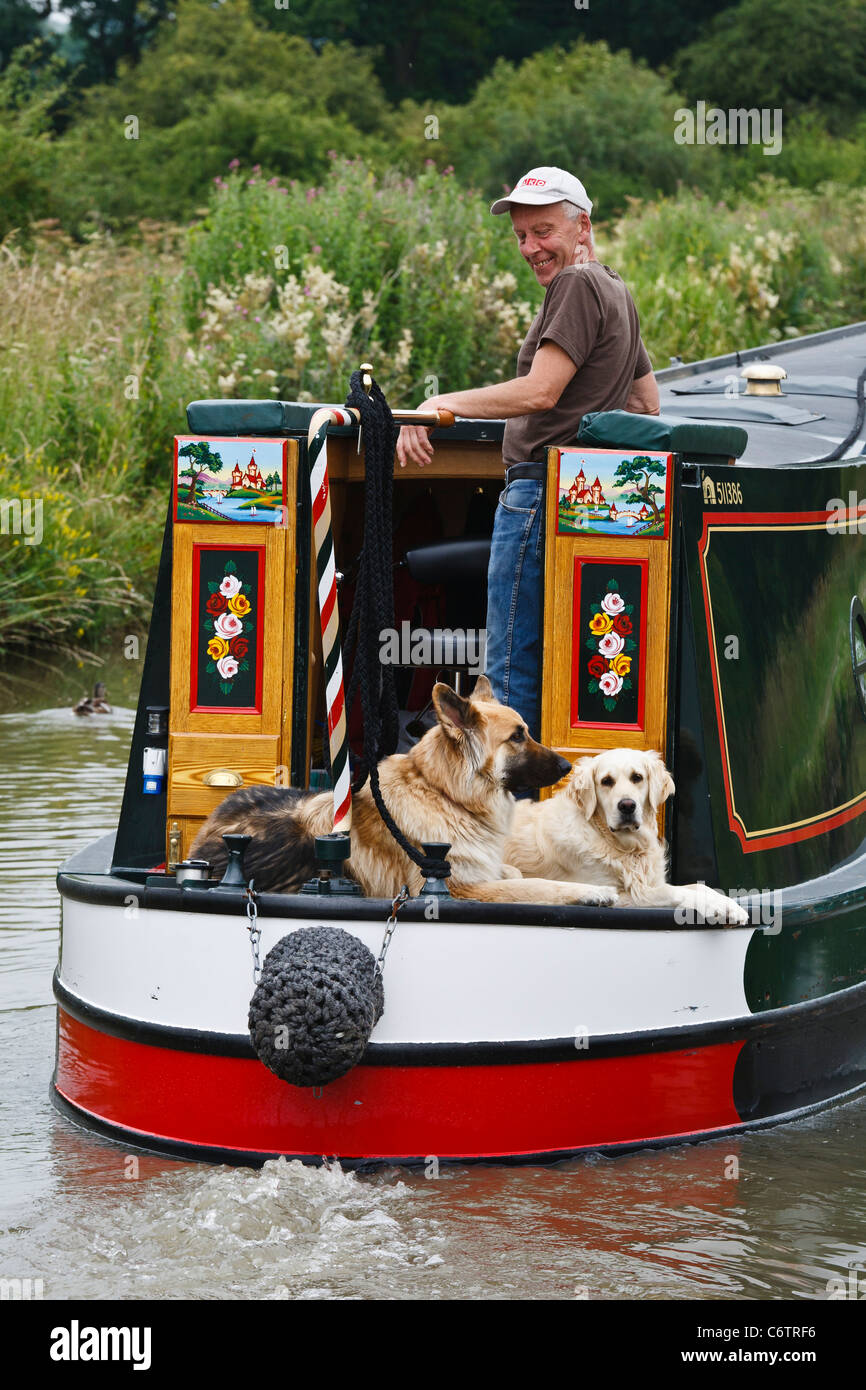 A narrowboater and his dogs on a traditionally built craft on the Oxford Canal near Braunston, Northamptonshire. - Stock Image