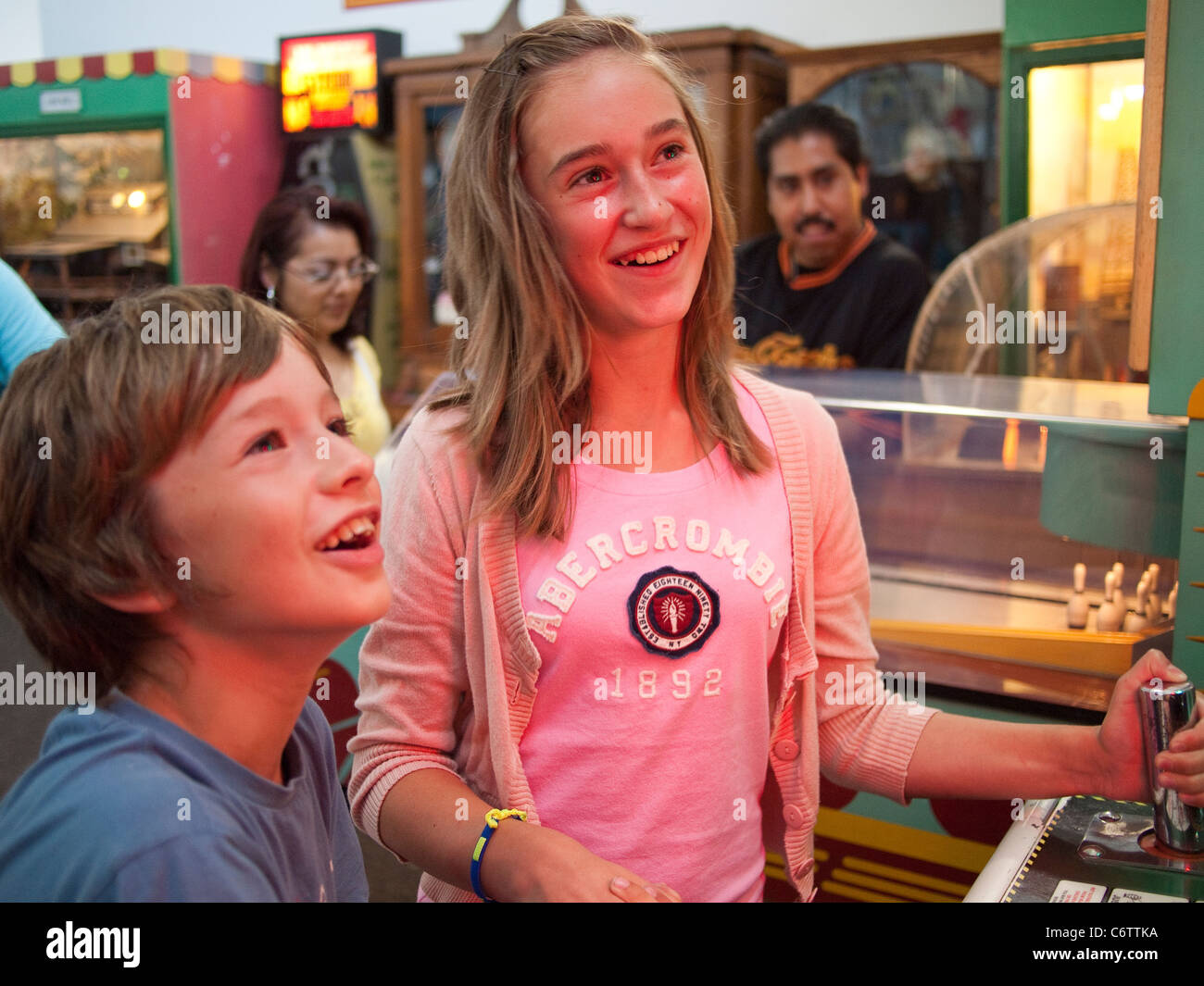 Brother and Sister Playing an Arcade Game - Stock Image