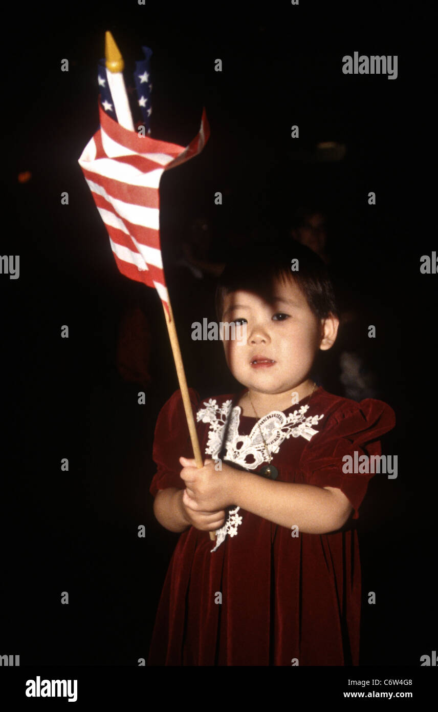 A young Korean girl waves an American flag during an immigration naturalization ceremony November 12, 1996 in Washington, - Stock Image