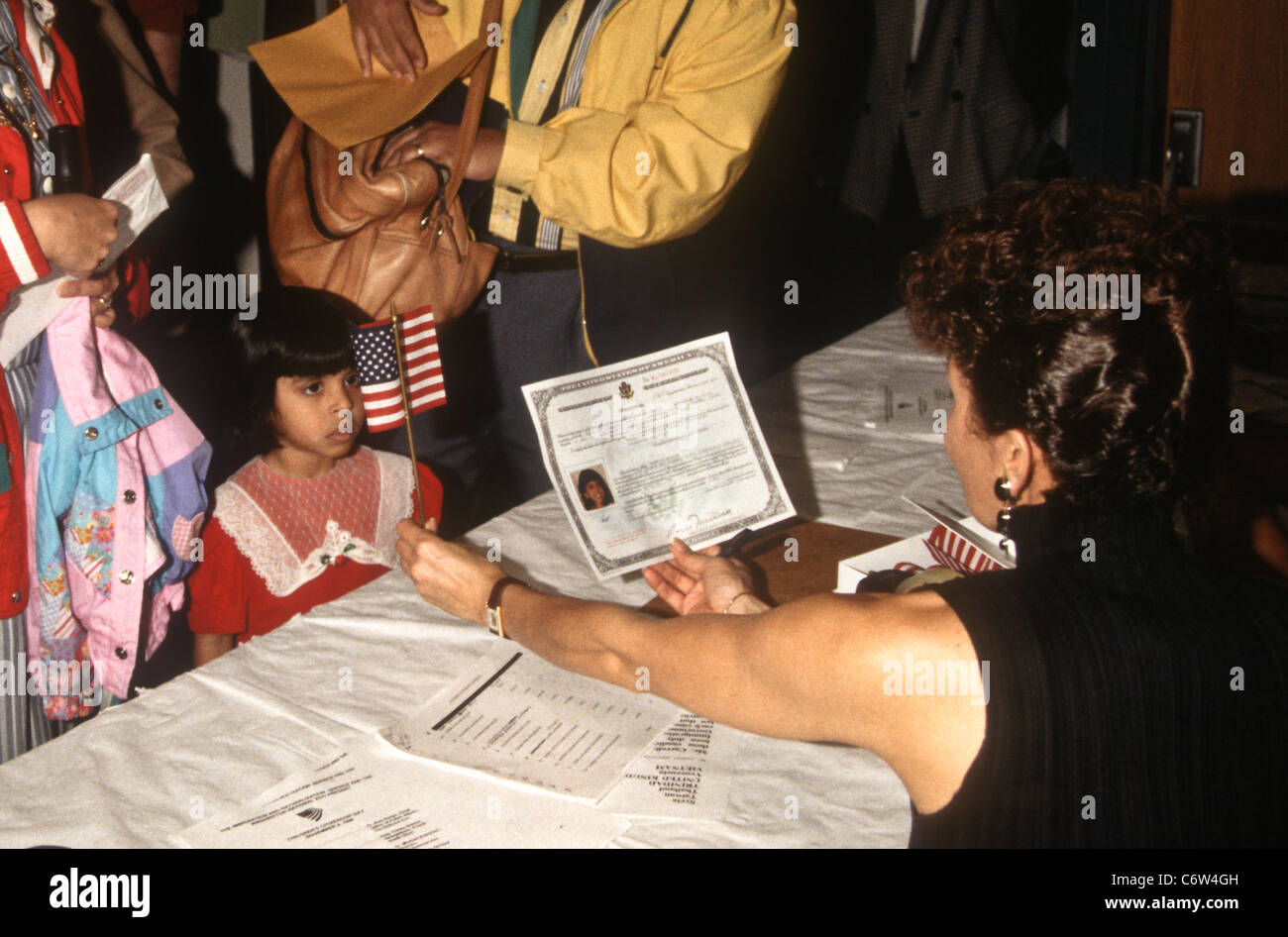 A young India girl is given an American flag during an immigration naturalization ceremony November 12, 1996 in - Stock Image