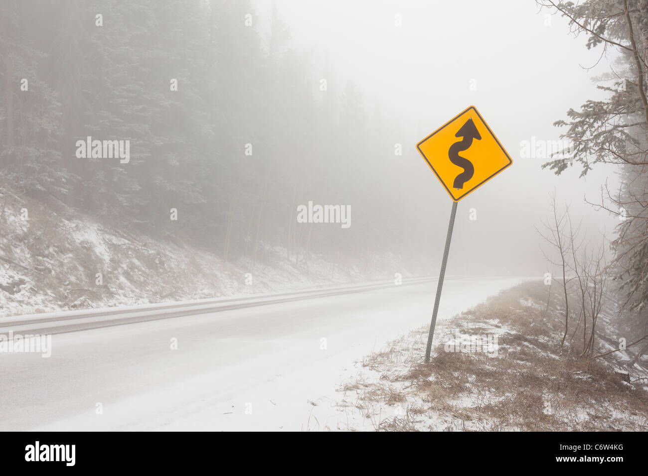 A curved road sign on a mountain road in snow and fog. - Stock Image