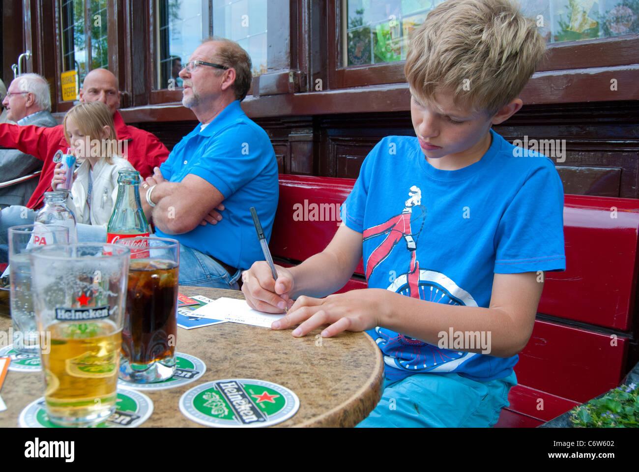 Boy writing postcards - Stock Image