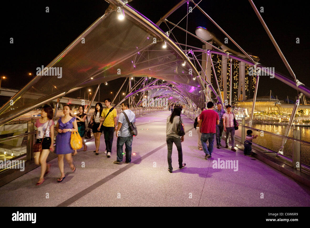 People walking along the modern Helix bridge with the marina Bay sands hotel in the background, the Marina, Singapore - Stock Image