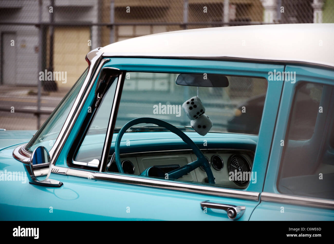 fluffy dice hanging from a car's rear view mirror - Stock Image
