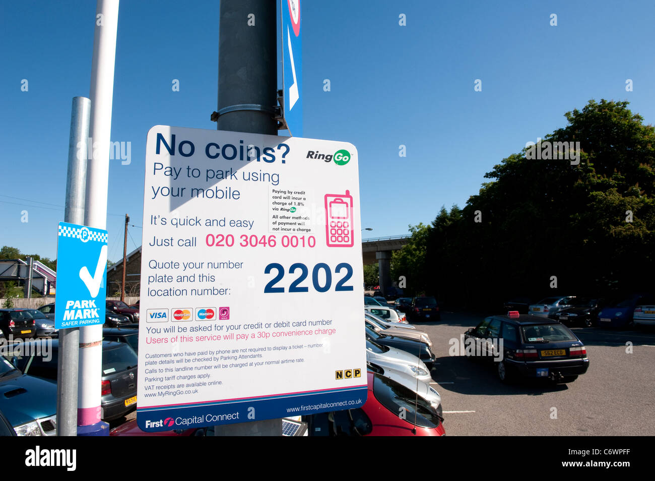 Sign in a busy railway station car park inviting visitors to pay for parking with their mobile phones. - Stock Image