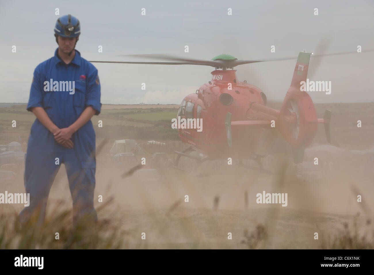 Coastguard Rescue Service volunteer oversees wales air ambulance taking off at Hillend Camping site, Llangennith, - Stock Image