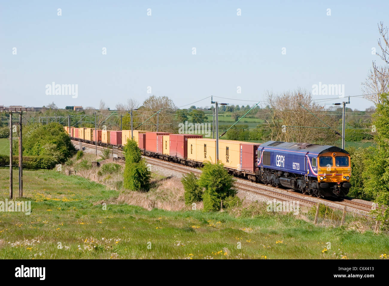 A GBRf owned class 66 diesel locomotive working an intermodal container freight train near Long Buckby. - Stock Image
