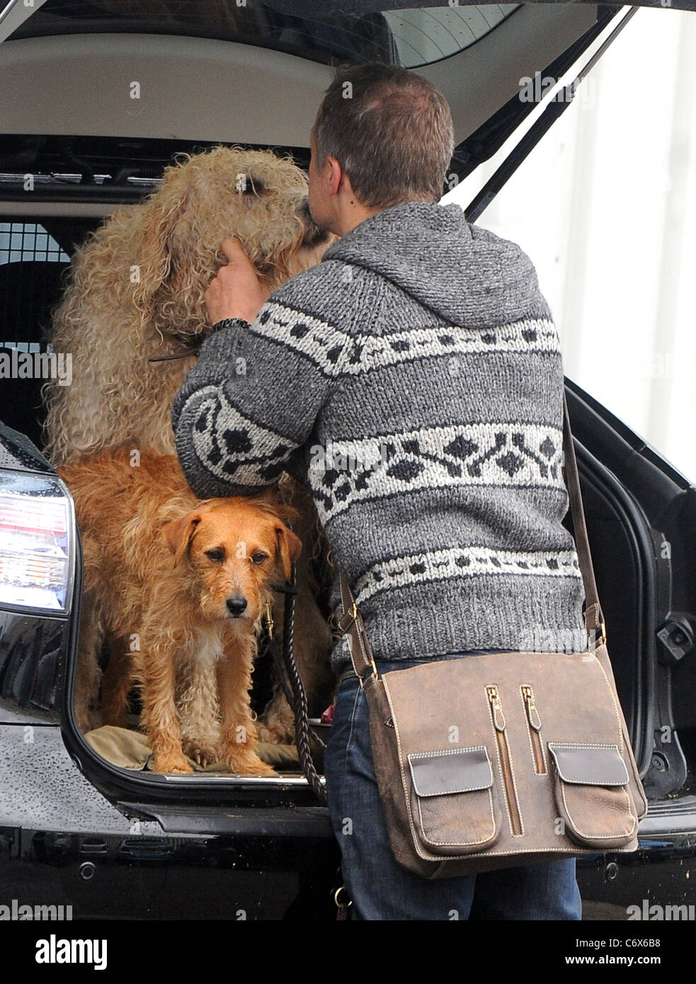 Graham Norton kisses his dog as he arrives at the Fountain Studios to record for BBC1 show 'Over The Rainbow' - Stock Image
