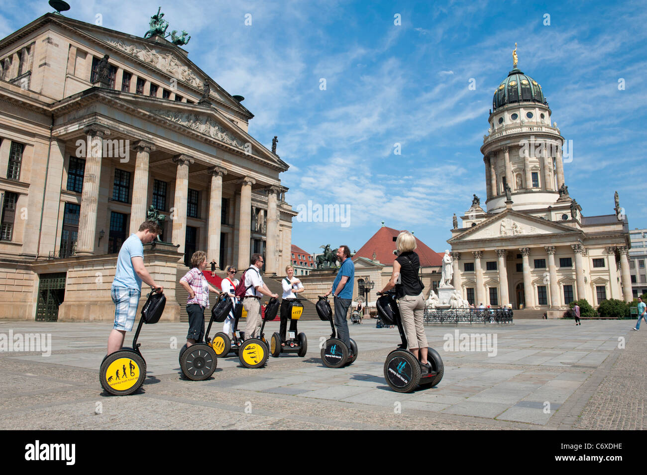 Tourists on segway tour in Gendarmenmarkt square and Konzerthaus and Franzosischer Dom in Mitte district of Berlin - Stock Image