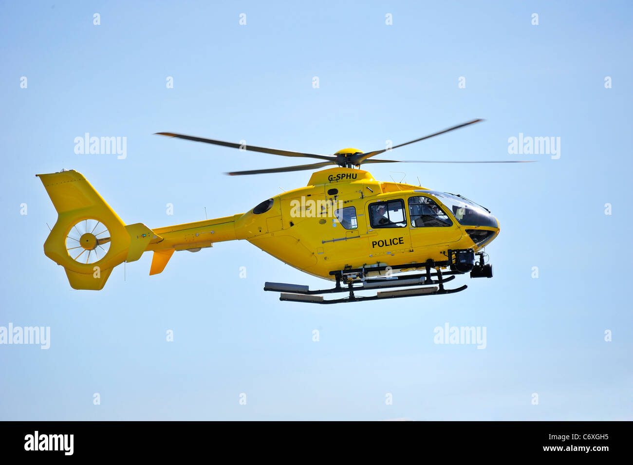 A helicopter of the Strathclyde Police force coming in to land against a clear blue sky - Stock Image