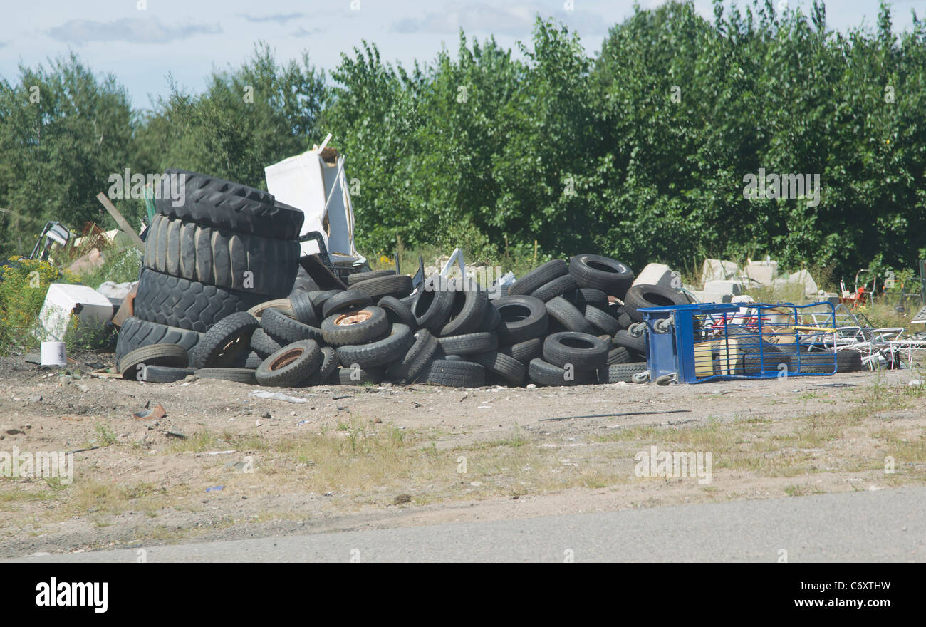 A big stack of old car and tractor tires waiting to be recycled at the county landfill. - Stock Image