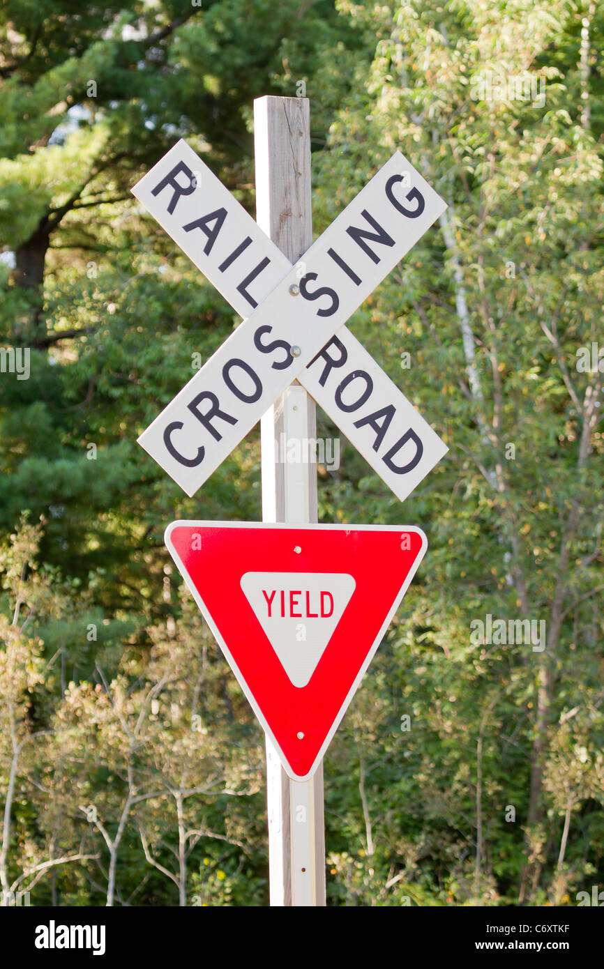 A red and white Yield sign at a Railroad Crossing intersection. - Stock Image