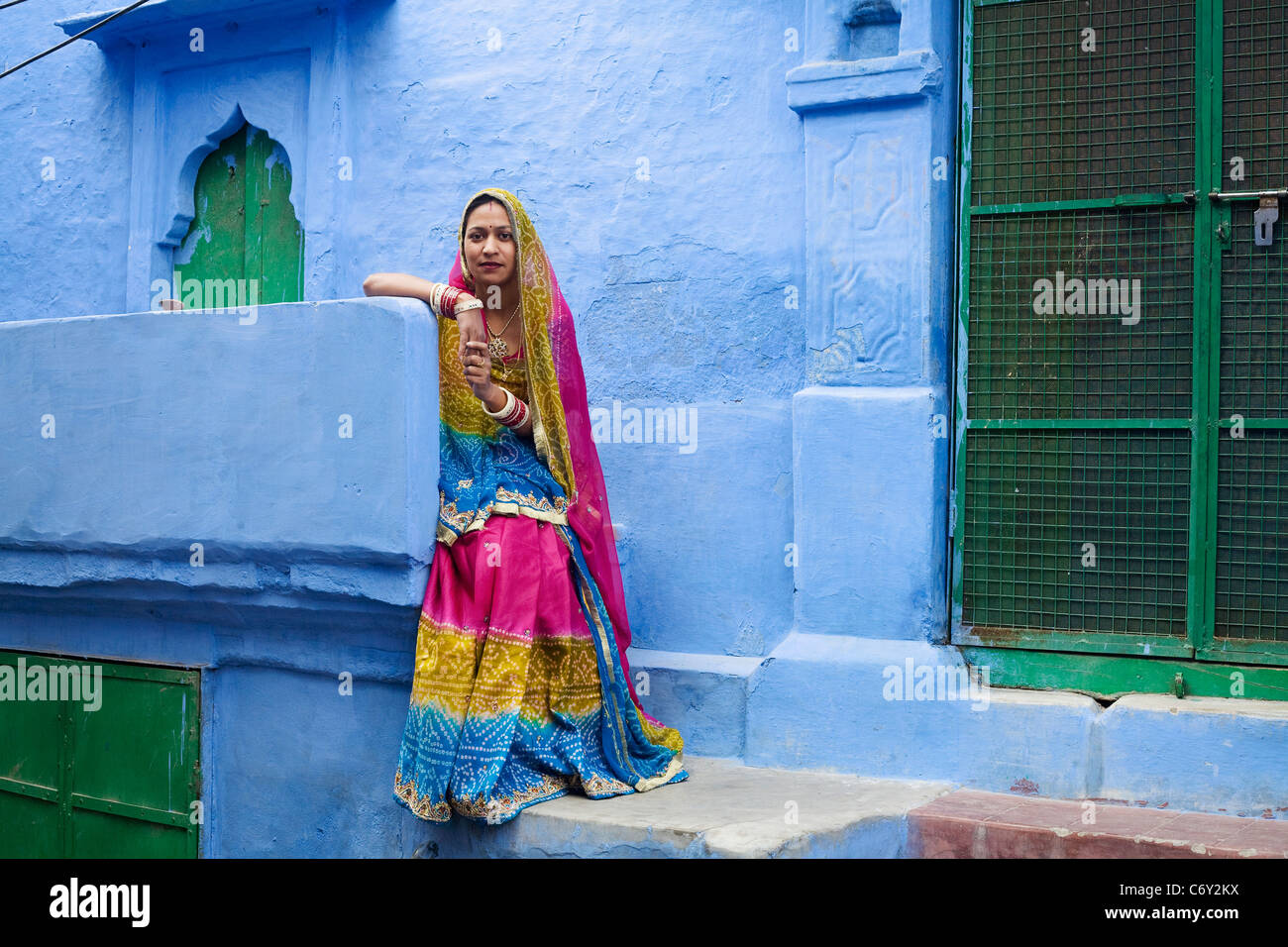 A woman of Jodhpur, India in Rajasthan state in traditional dress in front of one of the city's famous blue - Stock Image