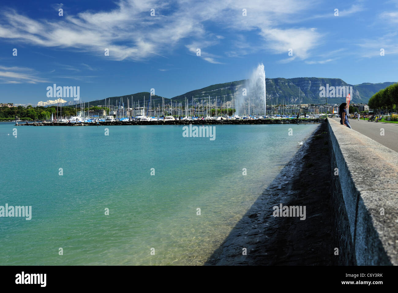 Lake Geneva, Switzerland aka Lac Leman, blue water with the water fountain and boats with the mountains and blue - Stock Image