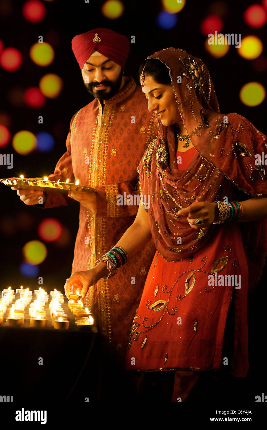 Sikh man holding a tray of diyas while the woman places them on a table - Stock Image