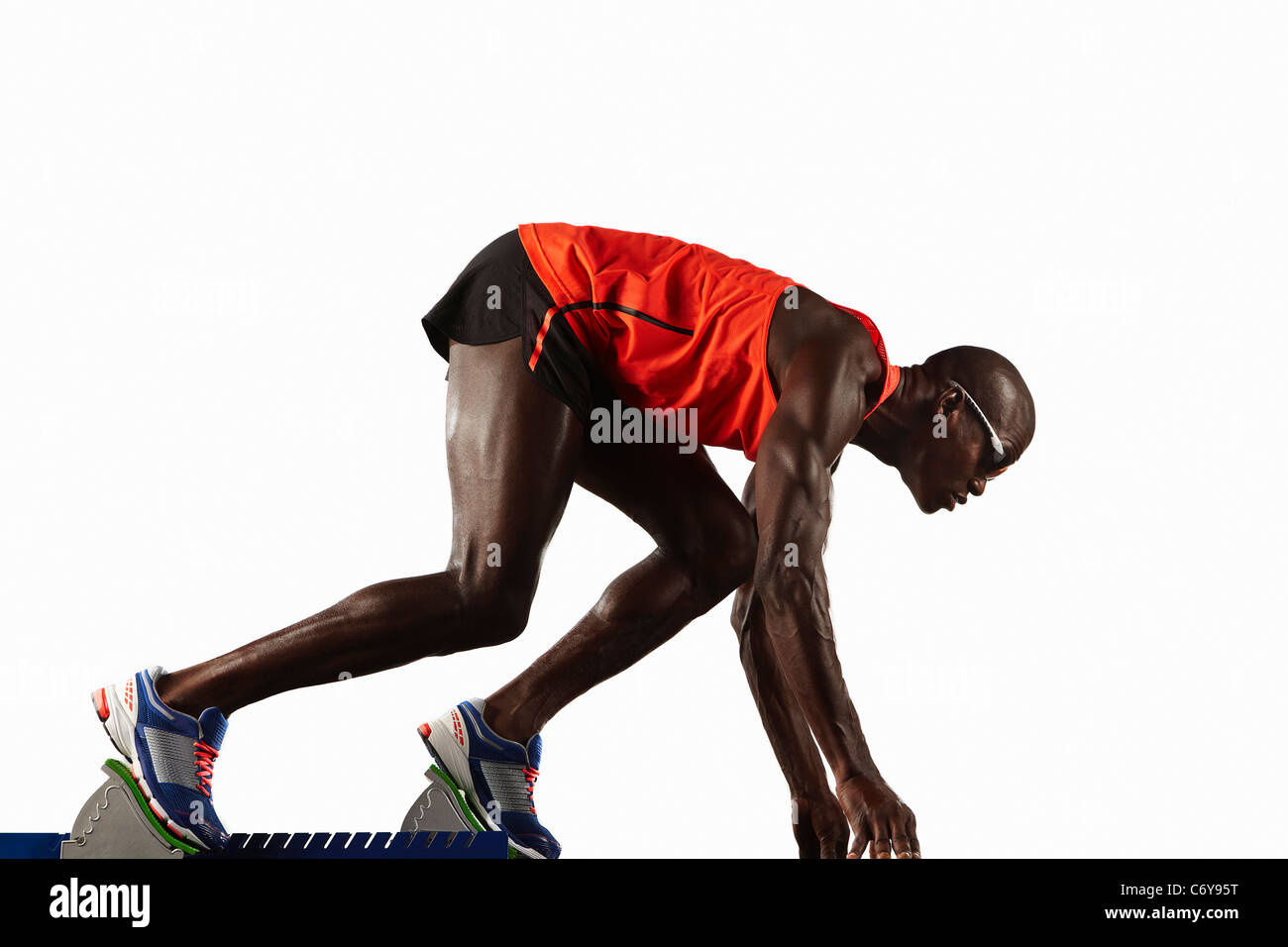 Runner crouched at starting line - Stock Image