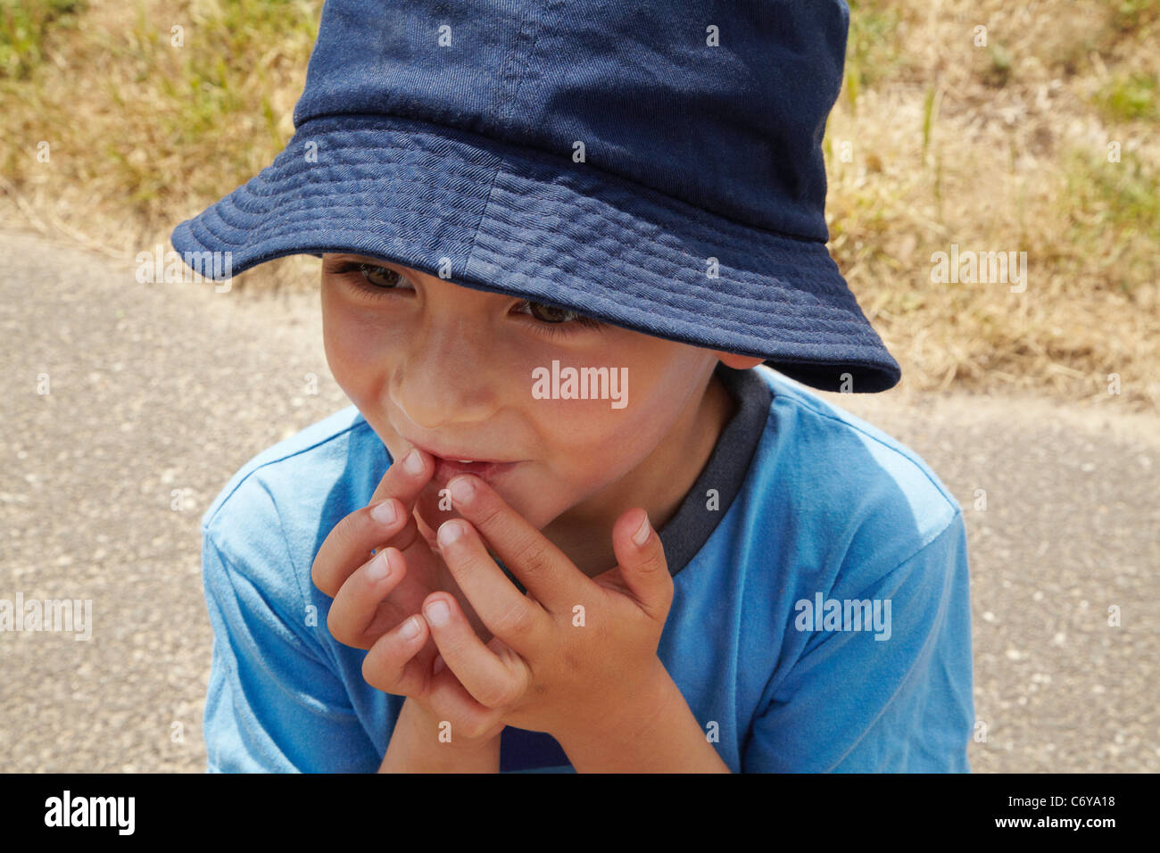 Curious boy touching his mouth Stock Photo