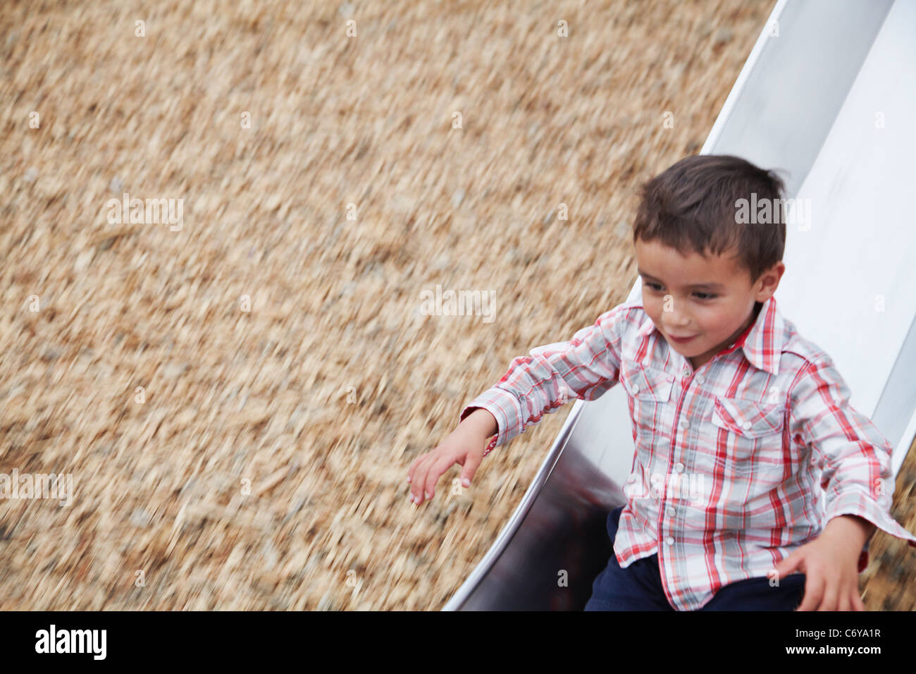 Boy playing on slide at playground - Stock Image
